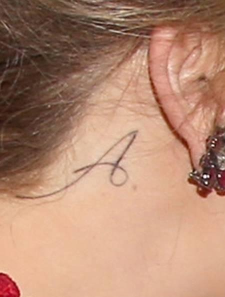 tatouage lettre derriere l'oreille