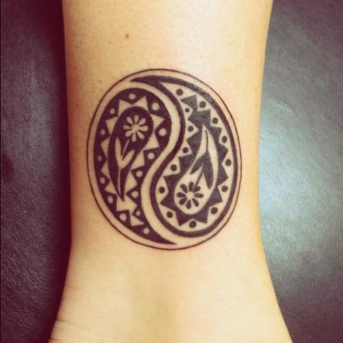 Le tatoueur a représenté un modèle de symbole ying yang très particulier  puisque ce sont deux petites fleurs qui sont au centre de chaque partie.